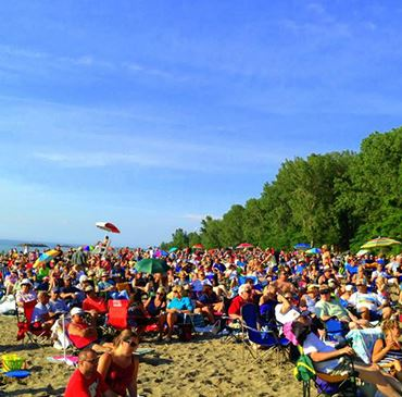 A large crowd of people gathered on a beach