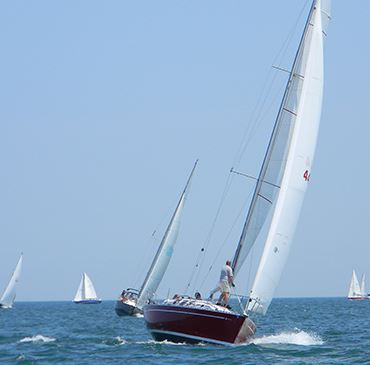 A sailboat leaning to one side from fierce wind while sailing on a large body of water